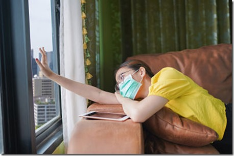 Young asian woman isolating at home with tablet on the sofa in the living room. She is bored because stay at home campaign for coronavirus prevention.